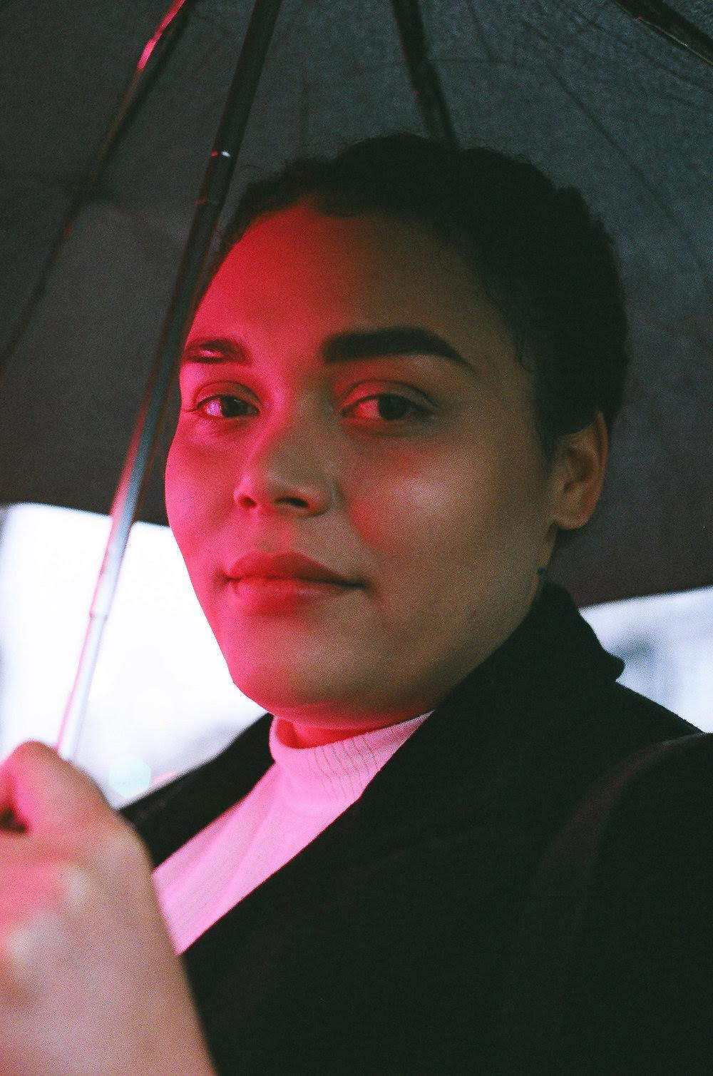 Photographed by Alyson Hardwick Image description: Sarah-Tai is a Black non-binary femme with olive-toned skin who wears a white turtleneck and a navy wool coat with their hair braided into a crown of loose two-strand twists. They stand in front of a neon light that casts a pinkish-red glow upon their face as they hold an umbrella and gaze at the camera.